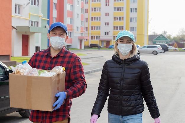 자원 봉사자들이 음식 상자와 함께 보호 마스크를 쓰고 길을 걸어
