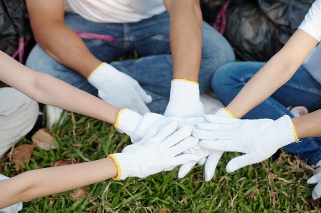 보호용 섬유 면장갑을 낀 자원봉사자들이 공원에서 쓰레기 수거를 시작하기 전에 손을 쌓고 있습니다