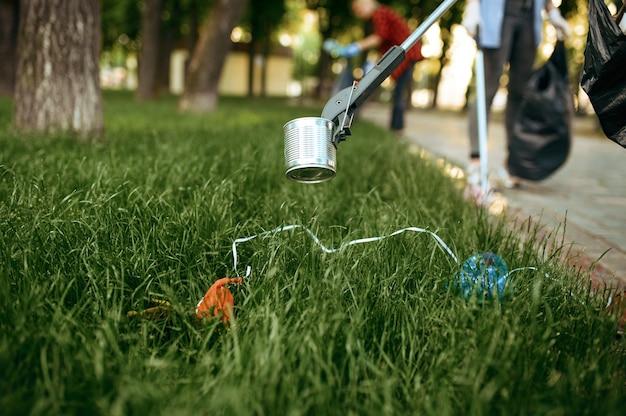 자원 봉사자들은 공원의 잔디에서 쓰레기를 줍고 자원 봉사합니다. 남성 사람이 숲을 청소, 생태 복원, 에코 라이프 스타일, 쓰레기 수거 및 재활용, 생태 관리, 환경 청소