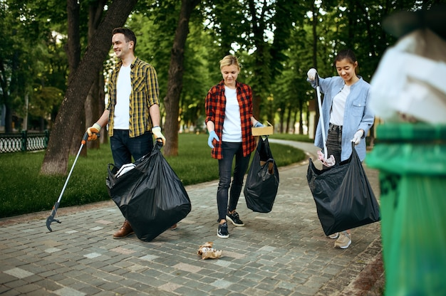 Volunteers picking trash in plastic bags in park, volunteering. male person cleans forest, ecological restoration, eco lifestyle, garbage collection and recycling, ecology care, environment cleaning
