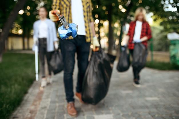 Volunteers picking trash in plastic bags in park, volunteering