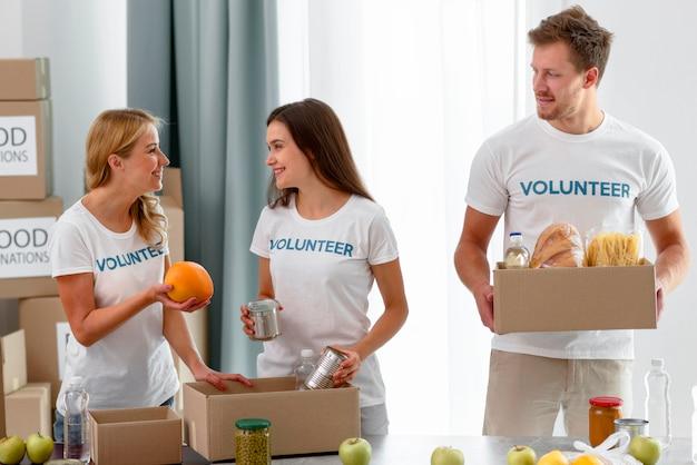 Volontari che preparano scatole con disposizioni per beneficenza