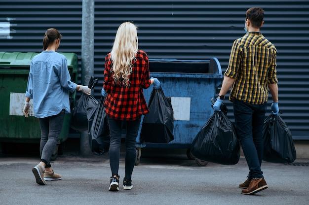 자원 봉사자들은 자원 봉사를하면서 플라스틱 쓰레기 봉투를 야외 캔에 넣습니다. 사람들은 도시 거리 청소, 생태 복원, 쓰레기 수거 및 재활용, 생태 관리, 환경 청소