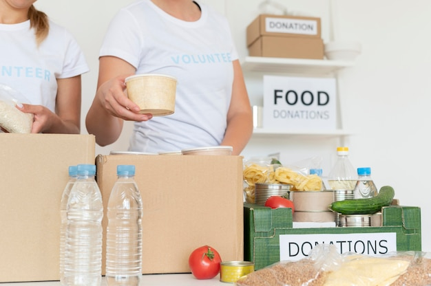 Volontari che mettono il cibo per la donazione nella scatola