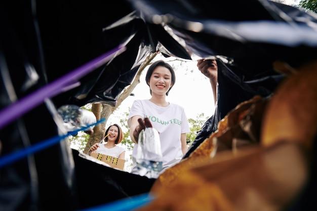 Volunteers putting garbage in sack