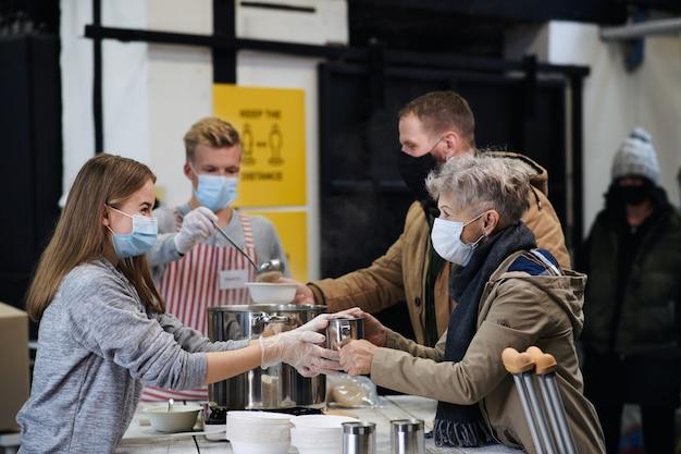 地域の慈善寄付センターで病気やホームレスのために温かいスープを提供するボランティア