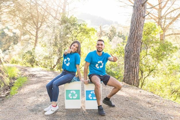 Volunteers sitting on garbage bins in woods