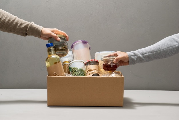 Волонтеры берут еду из коробки для пожертвований на столе