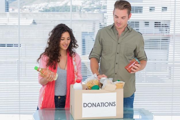 Волонтеры, вынимающие пищу из коробки для пожертвований