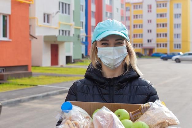 ボランティアは食料品の箱を持って通りを歩きます