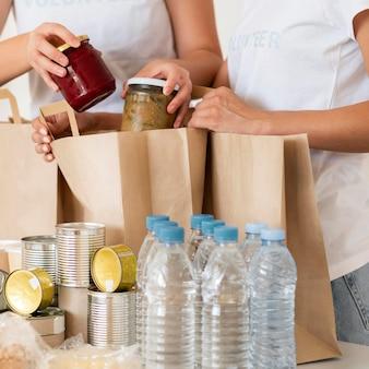 Волонтеры с мешками с едой и водой для пожертвований