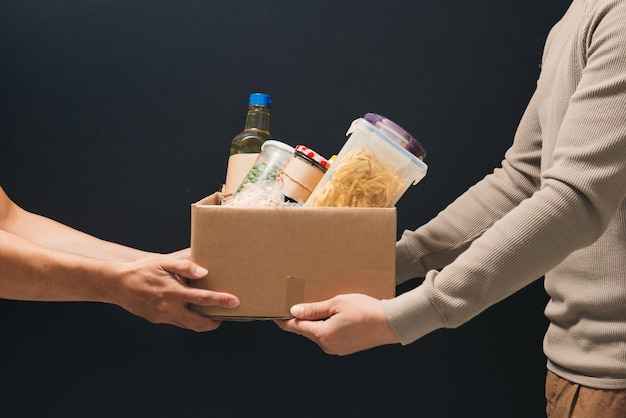 Volunteers with donation box with foodstuffs on dark