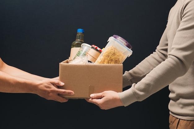 Добровольцы с коробкой для пожертвований с продуктами на темноте