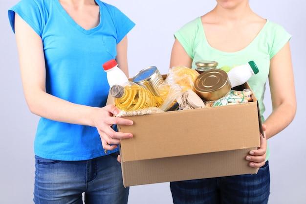 회색 표면에 식료품이 담긴 기부 상자가있는 자원 봉사자