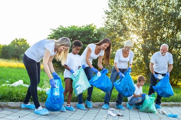 屋外でゴミを片付けるゴミ袋を持ったボランティア-エコロジーのコンセプト。