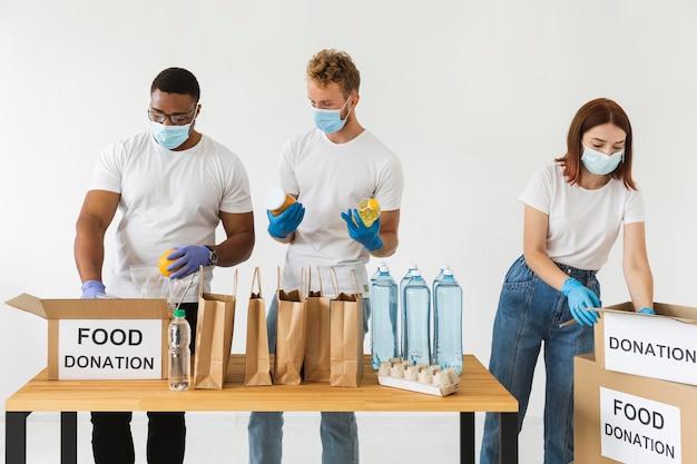 Волонтеры в перчатках и медицинских масках готовят еду для пожертвований с коробками