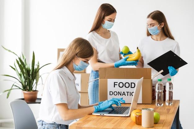 Волонтеры в перчатках и медицинских масках готовят еду в коробке для пожертвования