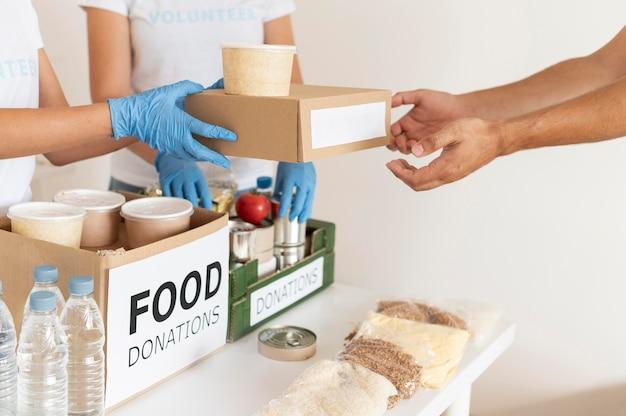 Добровольцы в перчатках передают коробки с продуктами для пожертвований