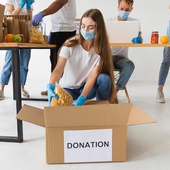 Volontari con maschere mediche e guanti che preparano scatole per donazioni con provviste