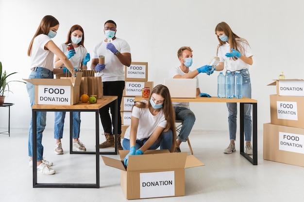 Volontari con maschere mediche e guanti che preparano scatole per le donazioni