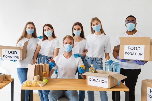 Волонтеры в медицинских масках позируют вместе с ящиками для пожертвований