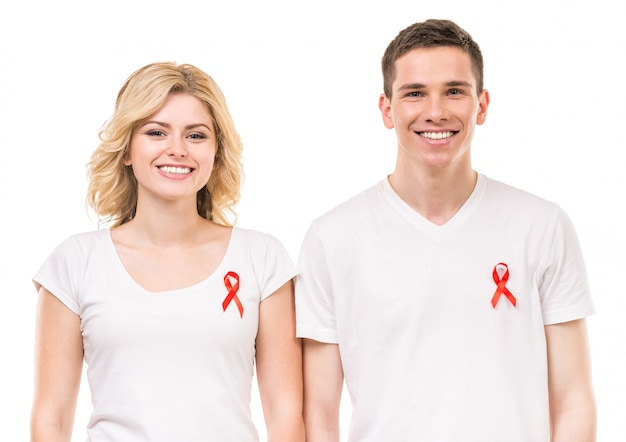 Volunteers with red aids ribbon standing on white.