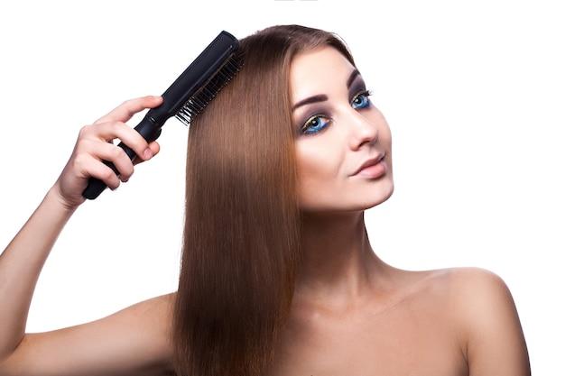 Сладострастная девушка с голубыми глазами расчесывает свои идеальные здоровые русые волосы расческой