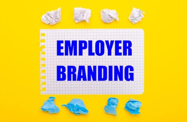 V на желтом фоне бело-синие скомканные листы бумаги и блокнот с надписью работодатель брендинг.