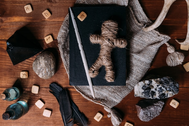 Voodoo doll made of rope lies on a black book, surrounded by magical ritual objects, flat lay
