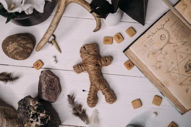 A voodoo doll made of rope lies with old book grimoire, surrounded by magical ritual objects, flat lay