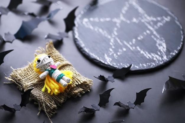 Кукла вуду на каменном фоне с драматическим освещением. мистический натюрморт с куклой вуду, картами таро, книгами, злыми свечами и предметами колдовства. обряд гадания.