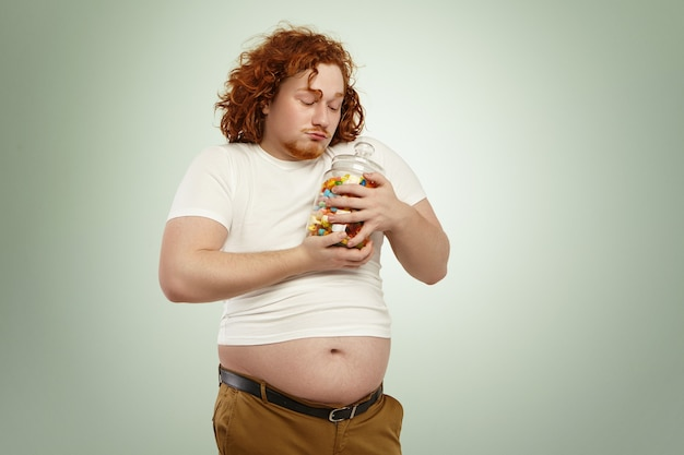 Voracious greedy fat man with red curly hair holding jar of sweets tight