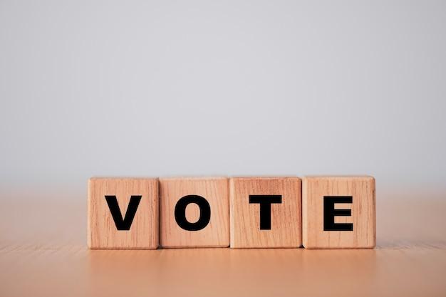 Концепция голосования и выборов, экран печати формулировок голосования на деревянном кубическом блоке.