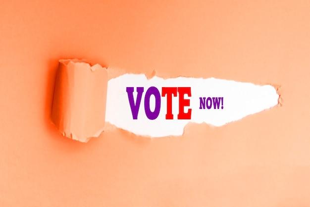 찢어진 종이에 쓰여진 영어로 된 지금 투표 문구