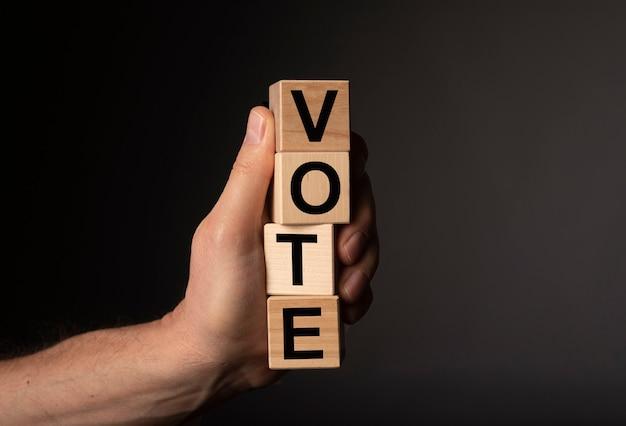 男性の手で木製の立方体に投票する