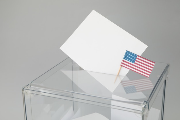 Voting box with bulletins and american flag on gray surface