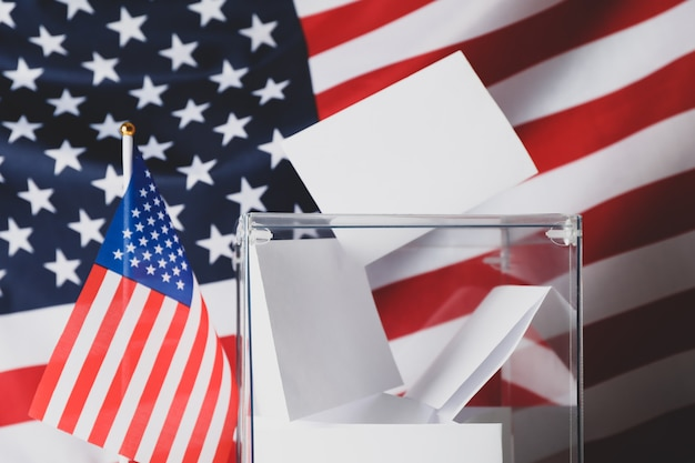 Voting box with bulletins on american flag