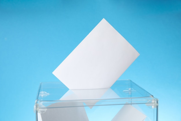 Voting box with bulletins on blue surface