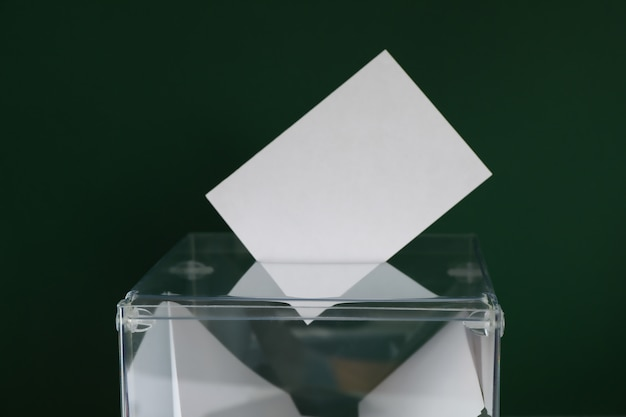 Voting box with bulletins on green surface