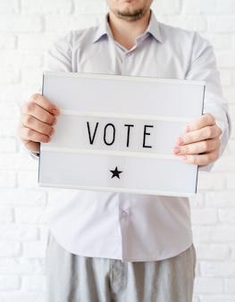 Концепция голосования. мужчина держит лайтбокс со словом голосование на фоне белого кирпича