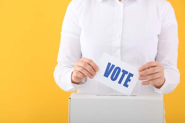 Voting woman near ballot box on color surface