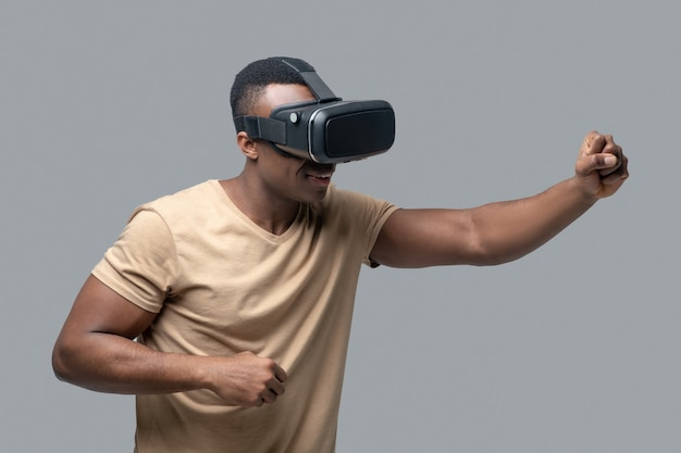 Vr. african american young man in vr glasses looking involved