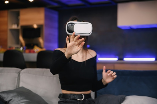 Vr. excited millennial girl using virtual reality headset playing videogame indoor. selective focus