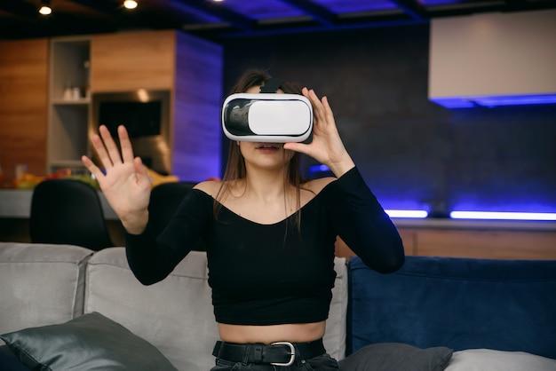 Vr. excited millennial girl с помощью гарнитуры виртуальной реальности игра в видеоигры в помещении. выборочный фокус