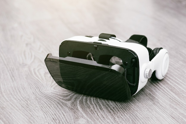 Vr glasses or virtual reality headset helmet on wood surface