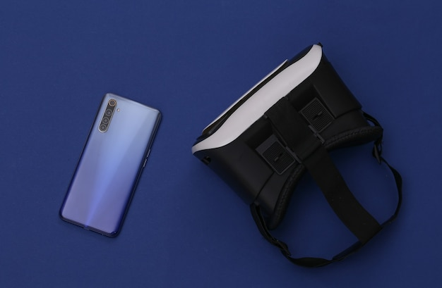 Vr headset and smartphone on classic blue background.