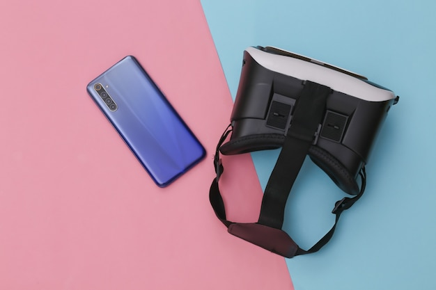 Vr headset and smartphone on pink blue pastel background.