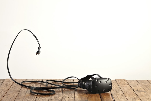 Vr headset and some cords on rough rustic wooden table on white wall