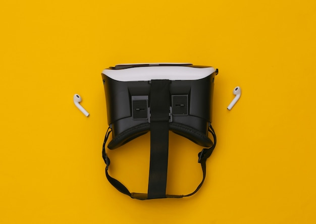 Vr headset and wireless headphones on yellow background.