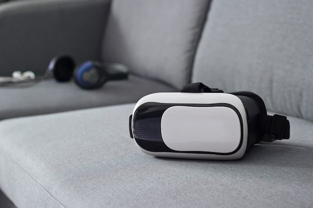 Vr headset with earphone and laptop on sofa in living room background